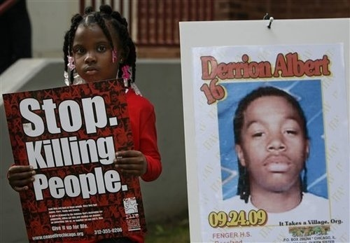 Nadashia Thomas, 6, a cousin of Derrion Albert, holds a sign beside a poster of  Derrion Albert at Fenger High School  in Chicago, Sept. 28, 2009. A vigil for Derrion Albert was planned outside of  Fenger High School. (AP Photo/Nam Y. Huh)